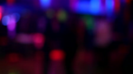 atividades : Night club life blur anonymous moving in dark with colored lights