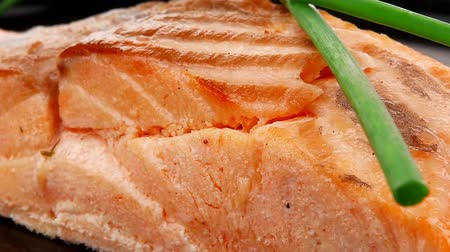 apetitoso : savory fish portion : norwegian salmon fillet roasted with green chinese onion  on black dish 1920x1080 intro motion slow hidef hd