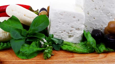 greek culture : dairy food : feta white cheese cubes and round served on wooden cut plate with green leaves and olive oil  Stock Footage