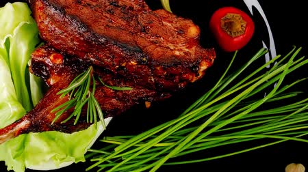 kapary : served meat: spiced barbecued ribs on black plate with vegetables 1920x1080 intro motion slow hidef hd Dostupné videozáznamy