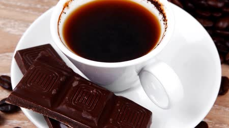 italian food : sweet hot food: black coffee with dark chocolate and coffee beans in bag on wooden table 1920x1080 intro motion slow hidef hd