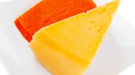 pieces of cheese : fresh dairy product : gourmet cheese triangles of yellow parmesan and orange cheddar on a plate 1920x1080 intro motion slow hidef hd Stock Footage
