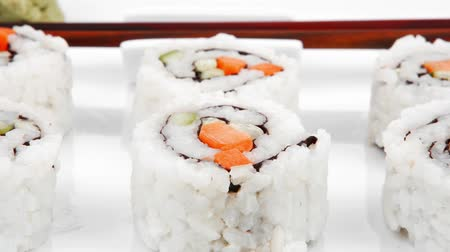orientalne : Japanese Cuisine - California Roll with Cucumber   Cream Cheese and Raw Salmon inside. Served with wasabi . Isolated on square plate 1920x1080 intro motion slow hidef hd