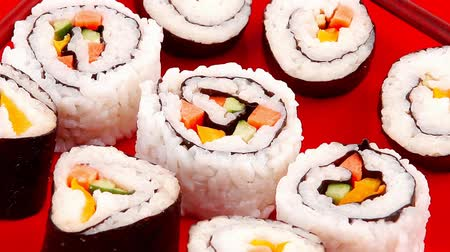 záběry : Japanese Cuisine : Sushi Maki Roll with Vegetables and Salmon inside . on red dish with sticks 1920x1080 intro motion slow hidef hd Dostupné videozáznamy