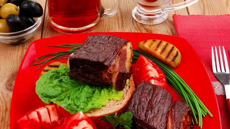 cielęcina : roast meat : beef (pork) steak garnished with vegetables   juice and olives on red plate over wooden table 1920x1080 intro motion slow hidef hd