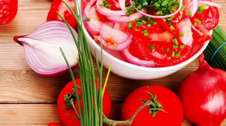 zöldségek : vegetable salad : fresh tomato salad in white bowl with bundle of chives   tomatoes on twig   onion  and garlic over wooden table 1920x1080 intro motion slow hidef hd Stock mozgókép