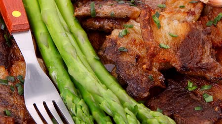 gourmet : dinner of hot beef pork meat grilled ribs with asparagus and garlic over wooden background table 1920x1080 intro motion slow hidef hd