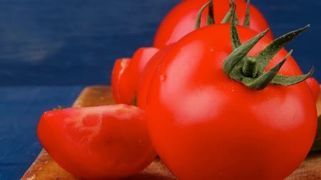 rajčata : raw vegetables : fresh raw ripe tomatoes on cutting board over blue table 1920x1080 intro motion slow hidef hd