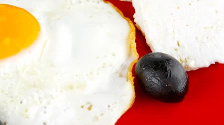 scrambled eggs : fried scrambled eggs eye with white goat feta cheese on red plate with black olives and vegetables 1920x1080 intro motion slow hidef hd