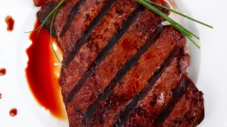 gourmet : fresh rich juicy grilled beef meat steak fillet with marks plate over wooden table decorated with sauces and cutlery new york style 1920x1080 intro motion slow hidef hd Stock Footage