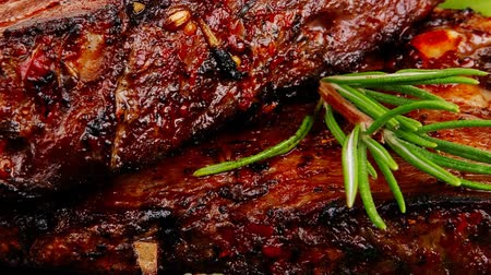 grelha : served meat: spiced barbecued ribs on black plate with peppers chives and capers 1920x1080 intro motion slow hidef hd