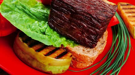 cielęcina : grilled meat : beef ( lamb ) garnished with vegetables   juice and olives on red plate over wooden table 1920x1080 intro motion slow hidef hd