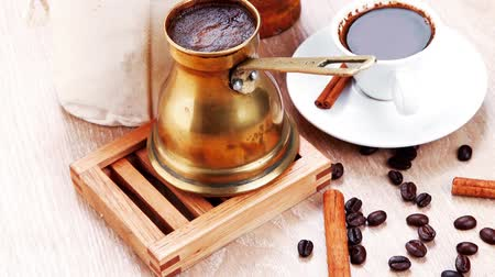 kopya : sweet hot drink : black arabic coffee in small white cup with mortar and pestle   bag full beans  copper old style cezve   decorated with cinnamon sticks and anise stars 1920x1080 intro motion slow hidef hd