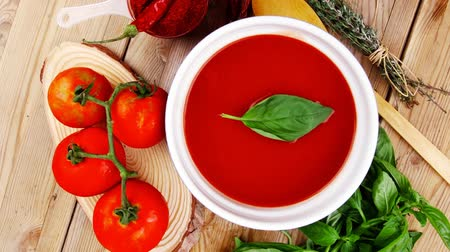 zupa : diet food : fresh cold tomato soup with basil thyme and dry pepper in big bowl on wood table 1920x1080 intro motion slow hidef hd