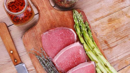 macro fotografia : meat food : raw beef fillet on cutting board with asparagus and thyme bundle   with color peppercorn mix and red paprika powder mixed with dry spices ready to cooking 1920x1080 intro motion slow hidef hd Vídeos