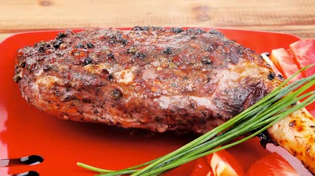 american cuisine : meat : grlled meat shoulder on red plate with tomatoes green lettuce over wooden table 1920x1080 intro motion slow hidef hd Stock Footage