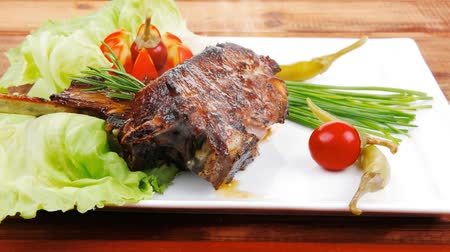 chives : meat plate on wooden table: roast ribs with tomatoes and red hot peppers 1920x1080 intro motion slow hidef hd