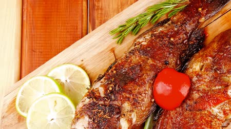 apetitoso : healthy food: two fried sea bass fish served with tomatoes and vegetables on big wooden board over table 1920x1080 intro motion slow hidef hd Stock Footage