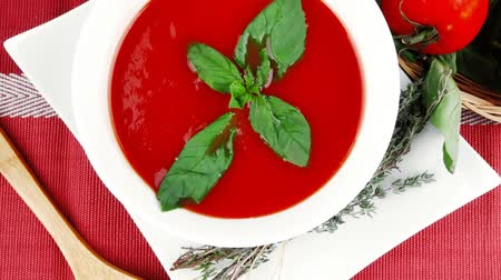 makro fotografie : cold fresh diet tomato soup with basil thyme and dry pepper in big bowl over red mat on wood table ready to eat 1920x1080 intro motion slow hidef hd