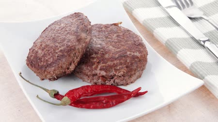 столовые приборы : fresh juicy beef meat hamburger with dry pepper plate over tablecloth with cutlery 1920x1080 intro motion slow hidef hd