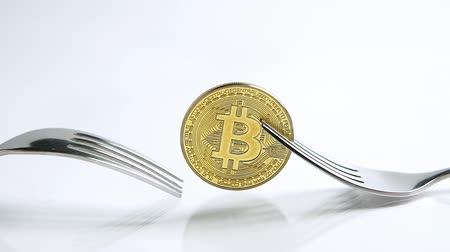 příloha : Static shot of Bitcoin fork concept with fork sliding away on the white background with reflection