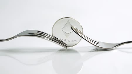 vantagem : Slide zoom in focus shot of Ethereum fork concept with Ethereum coin and two forks on the white background