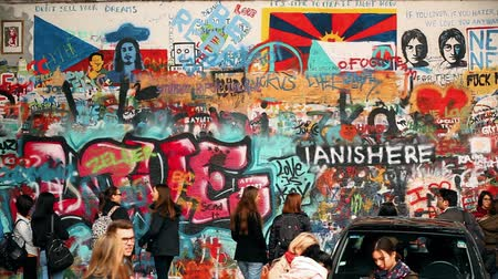 john : Prague, Czech Republic. People walking and taking photo in famous place in Prague - The John Lennon Wall. Wall filled with Lennon inspired graffiti and lyrics from Beatles songs Stock Footage