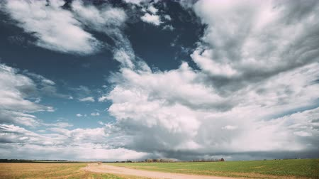 bělorusko : Time Lapse Time-lapse Timelapse Of Countryside Rural Road Through Field Spring Meadow Landscape Under Scenic Dramatic Sky With Fluffy Clouds Before Rain. Agricultural And Weather Forecast Concept