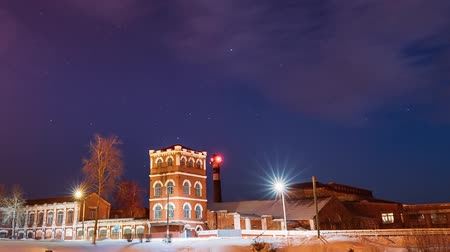 seasons changing : Dobrush, Gomel Region, Belarus. Time Lapse Time-lapse Timelapse From Evening To Night Of Old Paper Factory Tower In Winter Season. Night Stars Sky Above Historical Local Landmark