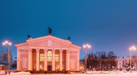 bělorusko : Gomel, Belarus. Time Lapse Time-lapse From Day To Night. Traffic And Light Trails Near Building Of Gomel Regional Drama Theatre On The Lenin Square In Winter Season. Change Of Day To Night