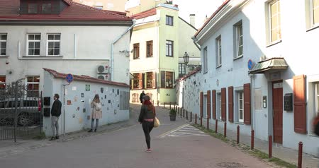 поэт : Vilnius, Lithuania - September 29, 2017: People Walking Near Literatu Street - One Of The Oldest Streets In The Old Town Of Vilnius, Lithuania. Wall Literary Works Of Art. Literatu Street Wall Стоковые видеозаписи