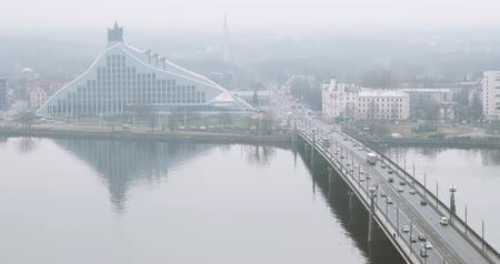tilts : Riga, Latvia - December 19, 2017: Top View Traffic On Akmens Tilts - Stone Bridge And National Library Building In Misty Fog Rainy Winter Day. Famous Landmark On Daugava Bank
