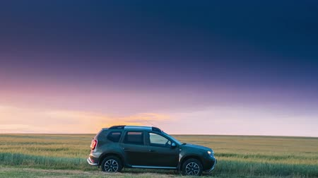 kompakt : Gomel, Belarus - June 22, 2018: Car Renault Duster Or Dacia Duster Suv In Road Through Summer Wheat Field In Amazing Sunset Time. Hyperlapse Time Lapse Timelapse Time-lapse
