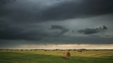 balé : Sky Before Rain With Rain Clouds On Horizon Above Rural Landscape Field Meadow With Hay Bales After Harvest. Time Lapse, Timelapse, Time-lapse