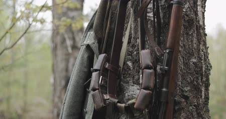 anti war : German Wehrmacht Infantry Soldiers Military Equipment Of World War II. Rifles, Flasks And Bag Tank For Anti-gas Hanging In Tree Trunk