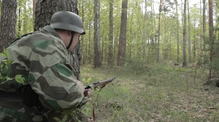infantaria : German Wehrmacht Infantry Soldier In World War II Shooting And Reloading Rifle In Forest. Soldier Attacking Enemy In Forest During Historical Reenactment