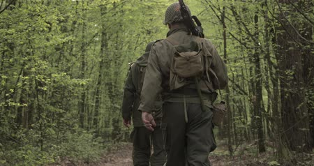 infantry : American Soldiers Of USA Infantry Of World War II Marching Walking Along Forest Road In Summer Day. Group of Soldiers Marching In Forest. Stock Footage