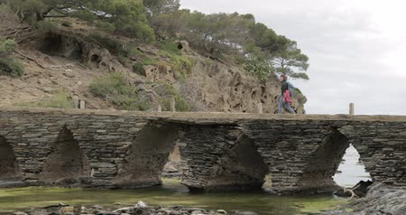 Коста : Cadaques, Province Of Girona, Catalonia, Spain. Young Woman Tourist Walking On Stone Bridge To Mirador.
