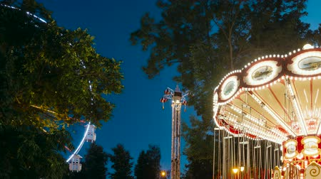 carrossel : Brightly Illuminated Rotating High Speed Carousel Merry-Go-Round. Summer Evening In City Amusement Park