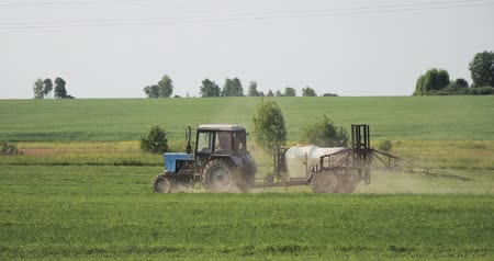 herbicides : Tractor With Fertilizer Spreader Spraying Pesticides Or Chemicals On Field With Sprayer At Spring