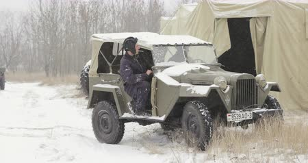 bérlet : Gomel, Belarus - November 25, 2018: Re-enactors Dressed As Russian Soldiers Of World War II drives Soviet WWII Army Truck GAZ-67 Car In Winter Forest. WWII Equipment Of Red Army Stock mozgókép