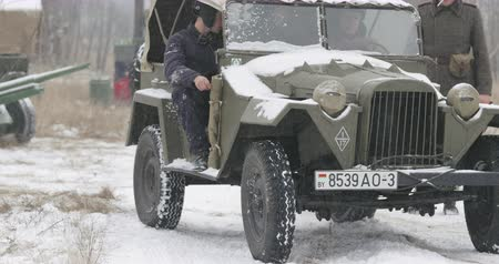 wwii : Gomel, Belarus - November 25, 2018: Re-enactors Dressed As Russian Soldiers Of World War II drives Soviet WWII Army Truck GAZ-67 Car In Winter Forest. WWII Equipment Of Red Army Stock Footage