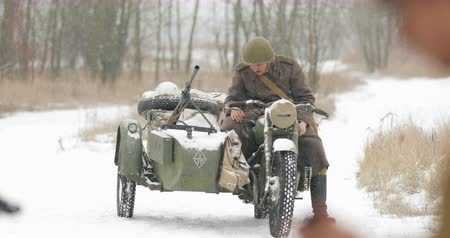 Gomel, Belarus - November 25, 2018: Re-enactor Dressed As Russian Soldier Of World War II Preparing For Battle Near Old Tricar, Three-wheeled Motorcycle With A Sidecar