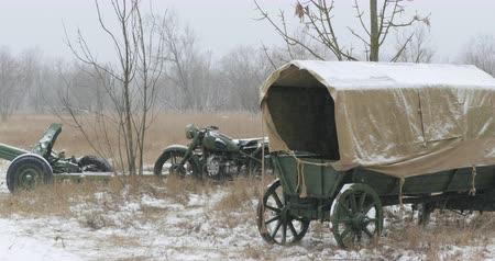 anti war : Abandoned Russian Soviet Equipment And Vehicles Of World War II. Russian Soviet 45mm Anti-tank Gun, Old Tricar Three-wheeled Motorcycle And Peasant Cart In Winter Snowy Day Stock Footage