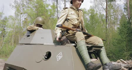Gomel, Belarus - April 29, 2018: Reenactors Dressed As Russian Soviet Red Army Soldiers Of World War II Sit Down In Armored Soviet Scout Car BA-64. Historical Reenactment In Forest
