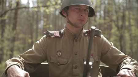 ba : Gomel, Belarus - April 30, 2018: Russian Soviet Crew Member Red Army Soldier Of World War II Sitting In Armoured Soviet Scout Car BA-64 In Forest. Stock Footage