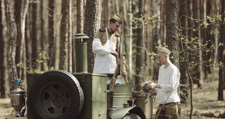 Gomel, Belarus - April 29, 2018: Reenactors Dressed As Russian Soviet Red Army Soldiers Of World War II Cooking Food In Field Kitchen In Forest Camp