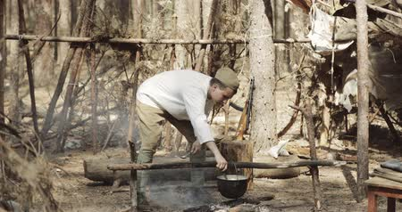 Gomel, Belarus - April 29, 2018: Reenactor Dressed As Russian Soviet Red Army Soldier Of World War II Cooking Food On A Fire In Forest In Forest Camp