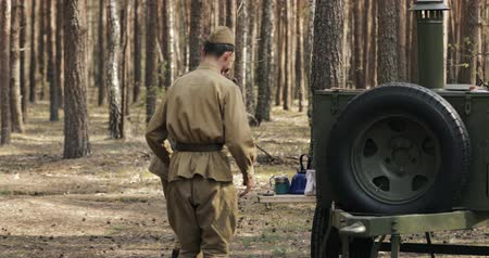urss : Gomel, Belarus - April 29, 2018: Reenactors Dressed As Russian Soviet Red Army Soldiers Of World War II Cooking Food In Field Kitchen In Forest Camp