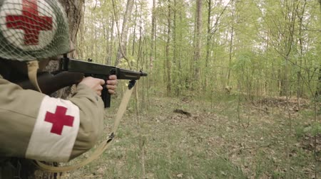 Gomel, Belarus - April 30, 2018: Soldier Of USA Infantry Medic Soldier Of World War II Aiming And Shooting From Submachine Weapon. American Soldier In Attack In Summer Forest Stok Video